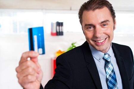 Smart looking male executive showing cash card to the camera. Happy face photo