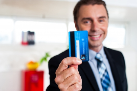 formals: Businessman in formals holding up his credit card and showing to the camera. Stock Photo
