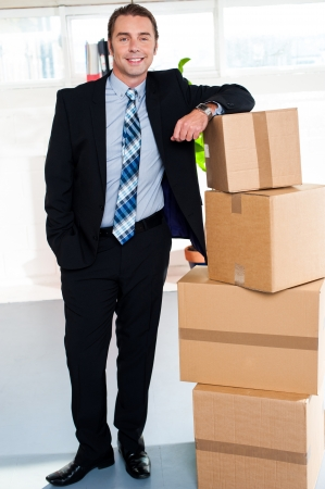 relocated: Young businessman relocated to new upgraded office. Miscellaneous office stuff packed in cartons.