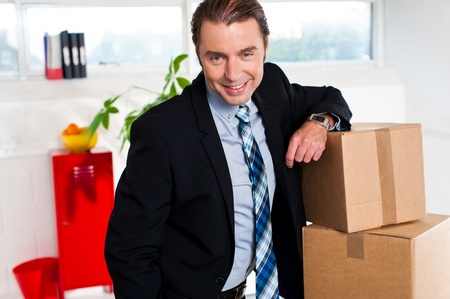relocated: Smiling businessman posing beside packed cartons, relocated in new office.