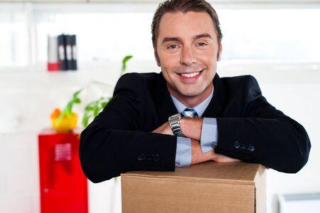 over packed: Sonriente hombre de negocios manteniendo los brazos cruzados sobre caja de cart�n llena y sonriendo a la c�mara. Foto de archivo