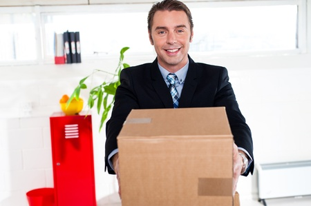 Business executive relocating his office. Needs some help, carrying packed carton alone. Stock Photo - 17204261