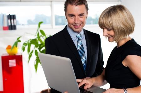 powerpoint: Fundador y Secretario discutiendo presentaci�n power point guardado en la computadora port�til.