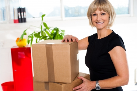 unpacked: Helper woman in office posing beside cardboard cartons ready to be unpacked. Stock Photo