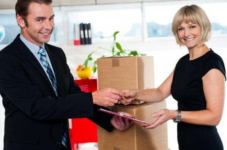 over packed: Boss consegna ricevuta cartoni imballati al suo segretario. Ufficio interno colpo. Archivio Fotografico