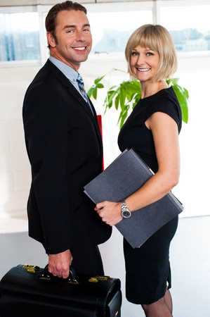 woman handle success: Ambitious businessman holding briefcase and posing with his female secretary. Stock Photo