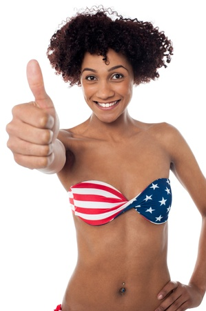 Sexy model in stars and stripes bikini showing thumbs up sign to the camera. Stock Photo - 17378626