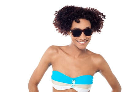 Curly haired slim bikini model wearing dark eye shades, smiling warmly. Stock Photo - 17378566