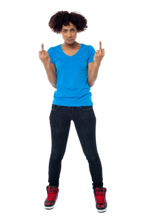 Studio shot of an annoyed young woman showing middle finger to you. Stock Photo - 17378494