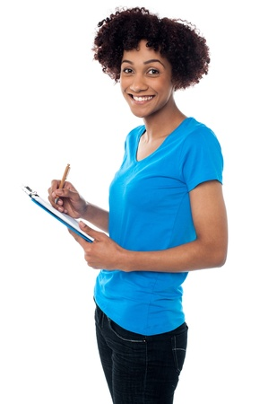Studio shot of young lady writing notes on clipboard, posing sideways. photo