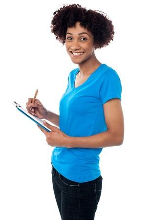 sideways: Studio shot of young lady writing notes on clipboard, posing sideways.