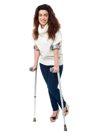 Isolation of a woman walking with help of crutches, full length portrait. photo