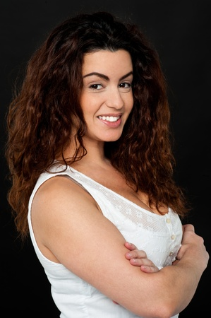 flirtatious: Confident gorgeous female model with perm long hair, standing sideways.