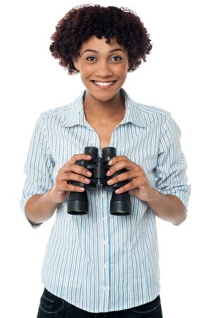 Curly haired female with binocular in hand smiling excitedly. Stock Photo - 17378687