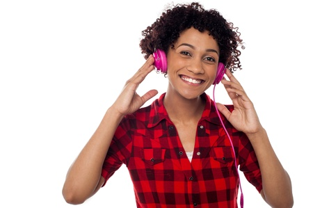 Cheerful young lady listening to lively music via pink headphones. Stock Photo - 17378624