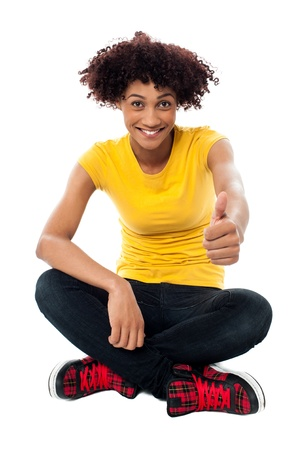 Isolated young girl gesturing thumbs up to the camera. Best of luck. Stock Photo - 17378636