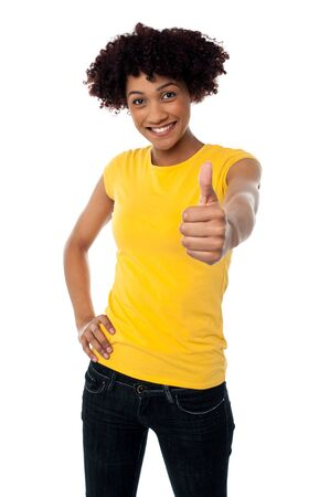 Cute looking female showing thumbs up sign to the camera, curly haired. Stock Photo - 17378577