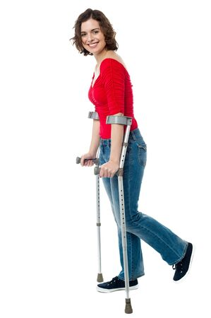 crutches: Full length portrait of smiling woman walking with the help of crutches