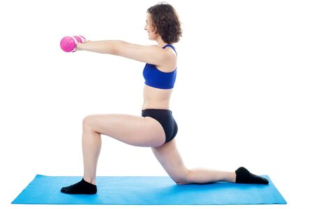 Isolation of a woman kneeling on one leg and holding dumbbells in her outstretched arms Stock Photo - 18253598