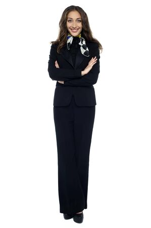 Stylish stewardess striking a confident pose with folded arms against white background. Stock Photo - 17489940