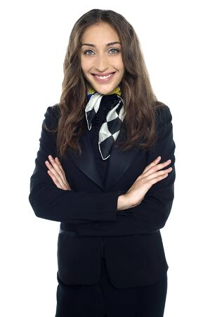 hotesse de l air: Plan profil de l'h�tesse de l'air gaie posant avec les bras crois�s sur fond blanc. Banque d'images