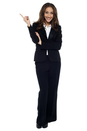 Young pretty businesswoman pointing away, full length studio shot. photo