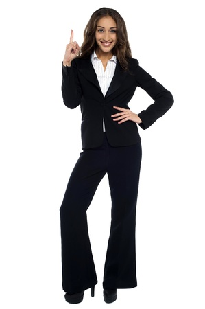 formals: Woman in formals pointing upwards, one hand on waist.