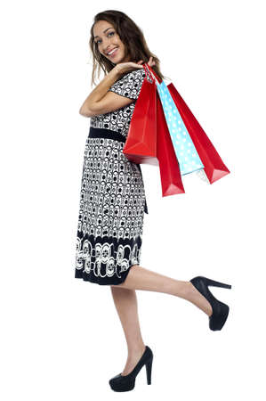 Woman wearing stilettos walking  back home with colorful shopping bags. photo