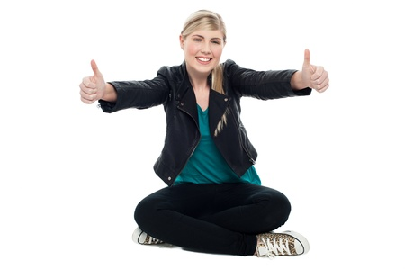 Attractive female sitting on the floor and gesturing double thumbs up. Stock Photo - 17490147