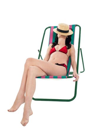 Alluring young bikini woman relaxing on reclining chair, covering her face wit hat. Stock Photo - 17560782