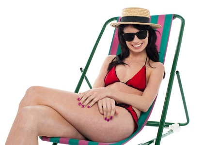 Studio shot of a bikini woman in shades and hat relaxing on reclining chair. Stock Photo - 17560786