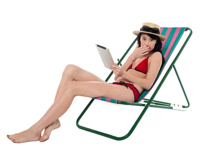 reclining chair: Shocked young bikini woman with tablet device in hand, lying on reclining chair.
