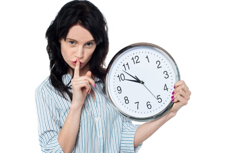 Serious faced young woman with wall clock in hand gesturing silence. Stock Photo - 17960396