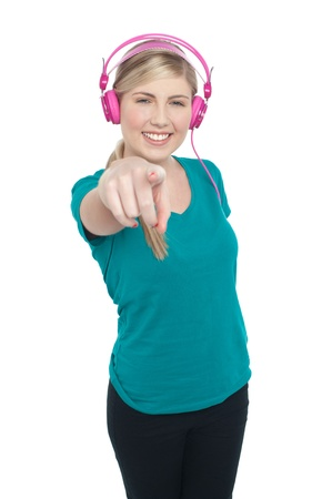Lovely blonde girl with pink headphones enjoying music and pointing you out. photo