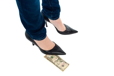 Cropped image of a woman in stilettos standing over ten dollar note. photo
