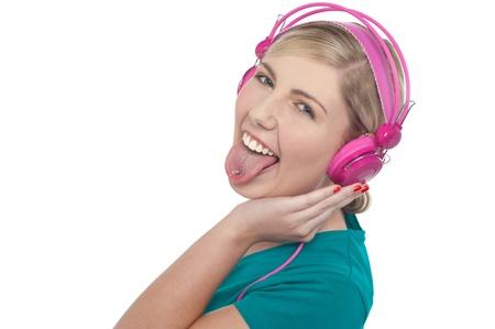 Fun loving blonde female with headphones on sticking her pierced tongue out. photo