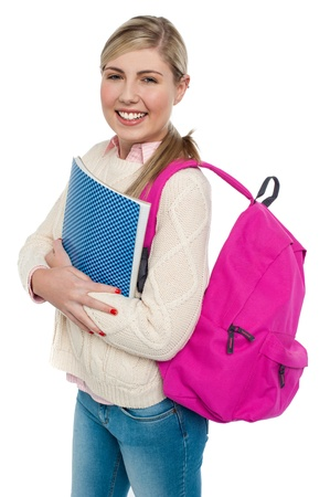 Teenage student with backpack and note book turning her face towards the camera. photo