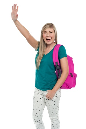 Excited blonde college student with backpack waving her hand to her friends. Stock Photo - 17490352