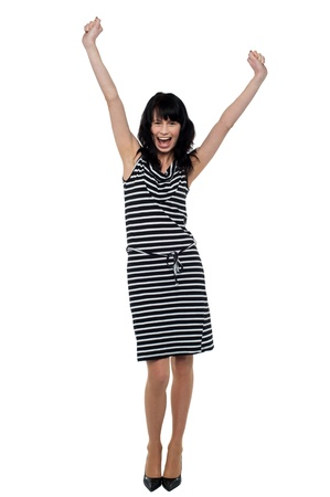 Full length portrait of a jubilant young woman celebrating her success. photo
