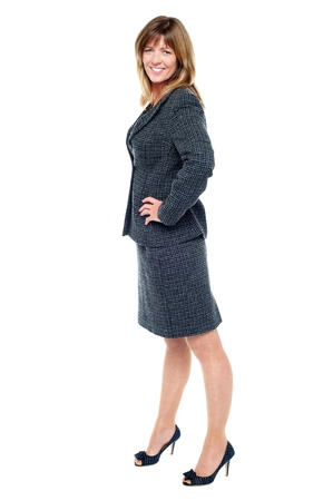 Full length portrait of a beautiful corporate lady in formals posing with hand on her waist. photo