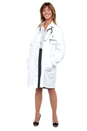 Full length portrait of pretty physician posing with hands in her coat pocket. photo
