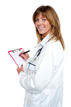 Isolated beautiful smiling physician writing on clipboard. photo