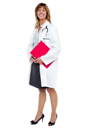 Full length portrait of cheerful female physician with clipboard and pen. photo
