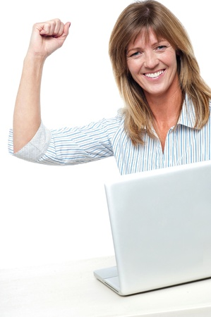 yup: Yup I have done it! Smiling executive at work place pumping her fist in joy. Stock Photo
