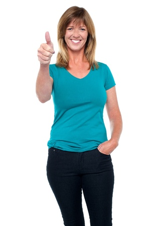 Fashionable middle aged blonde showing thumbs up sign to the camera. Stock Photo - 17643635