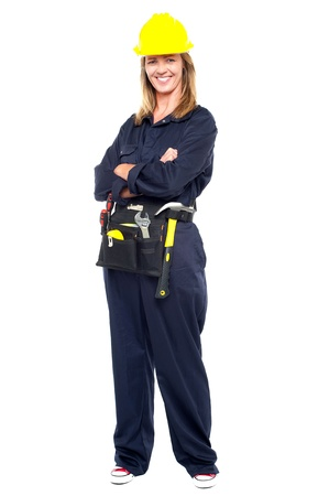 Full length portrait of smiling female worker wearing safety helmet and belt of tools. photo
