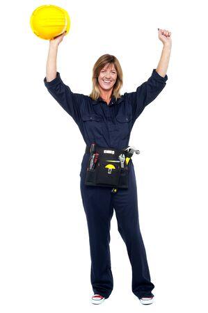 safety helmet: Emocionado mujer sosteniendo arquitecto casco de seguridad en los brazos levantados. Foto de archivo