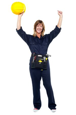 Excited female architect holding safety helmet in raised arms. photo