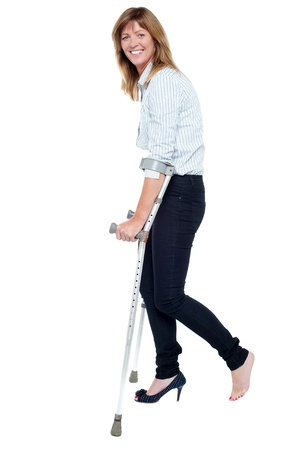 Smiling woman walking with help of crutches. Full length portrait. photo