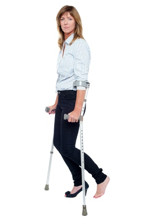 Sad woman with stiletto in one leg walking with the help of crutches.